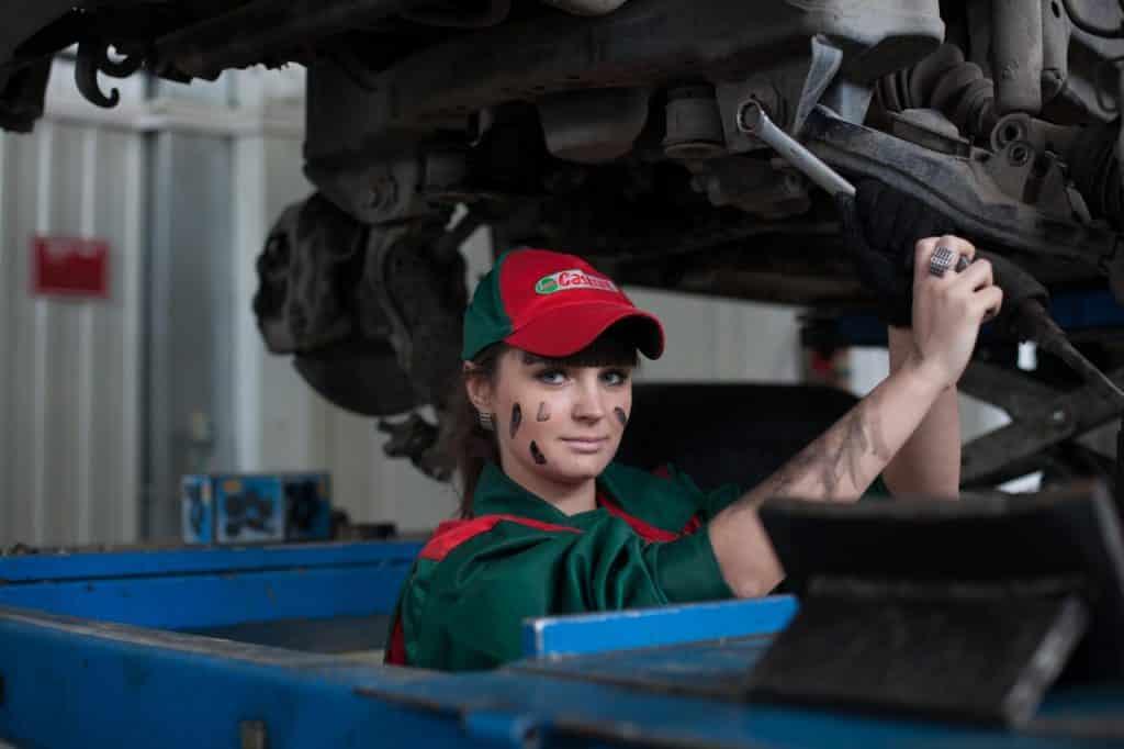 Femme garagiste travaillant sur une voiture nettoyant moteur
