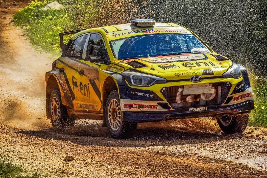 Voiture de rallye jaune en pleine course sur chemin