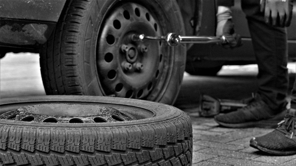 Homme entrain de changer un pneu avec clé