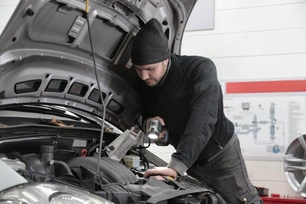 Garagiste contrôlant le moteur d'une voiture