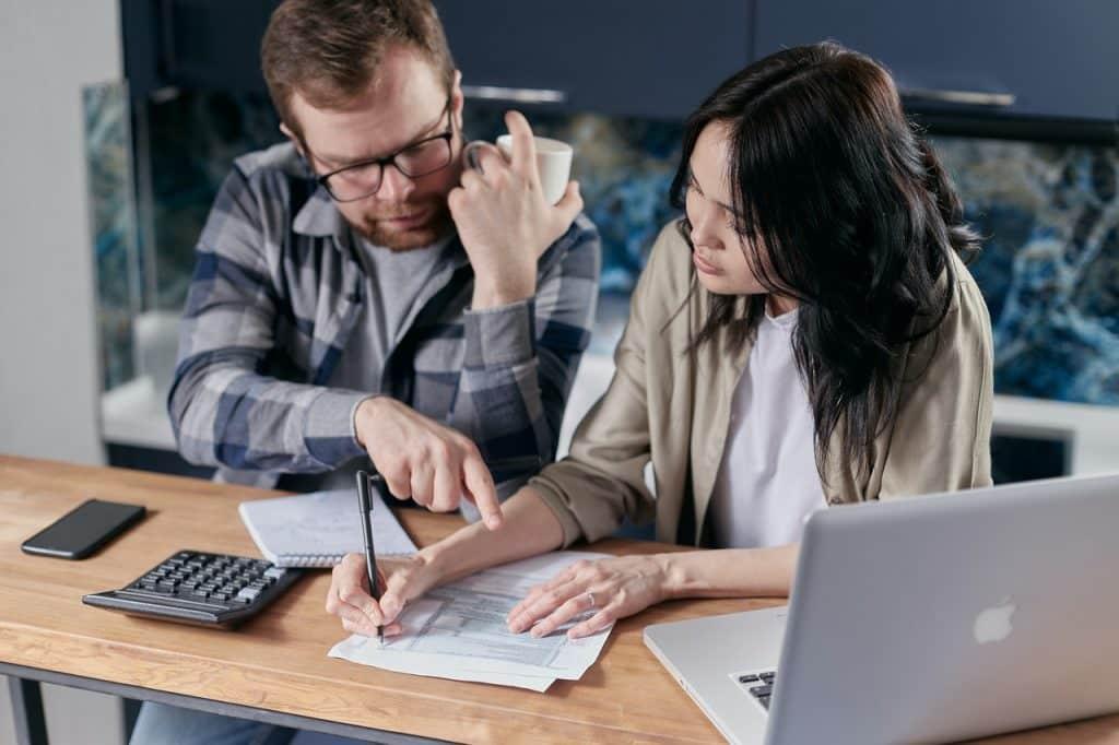 Couple calculant et définissant leur budget, avec calculette et ordinateur