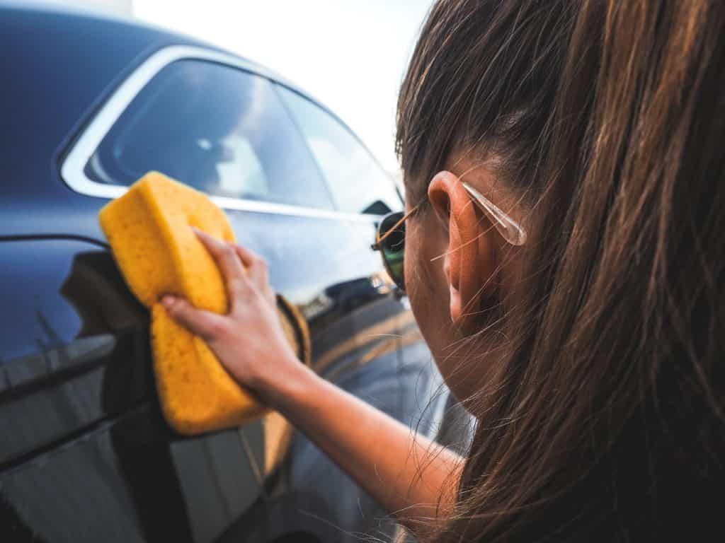 Femme lavant une voiture berline noire avec une grosse éponge jaune
