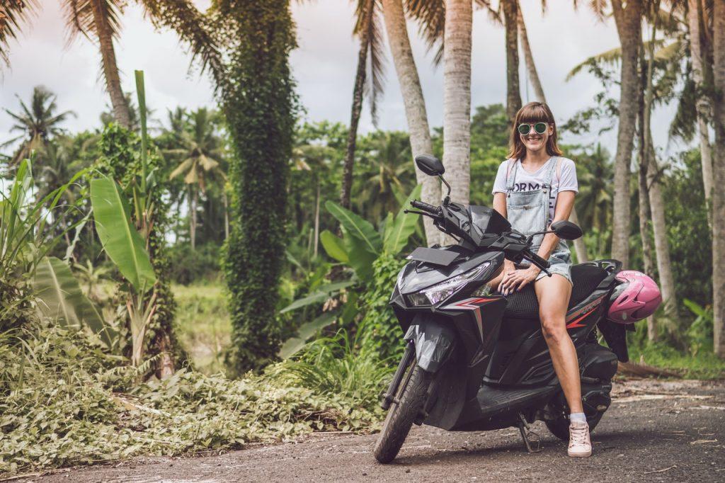 Femme souriante, sourire sur un scooter, palmier