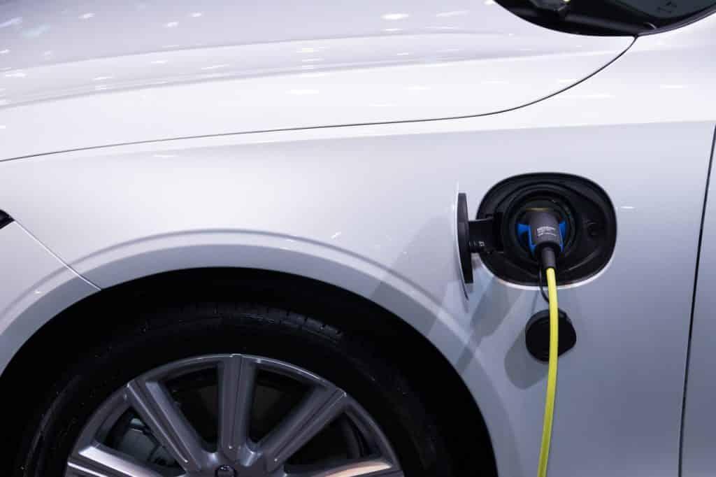 Voiture blanche électrique branchée à une prise pour se recharger