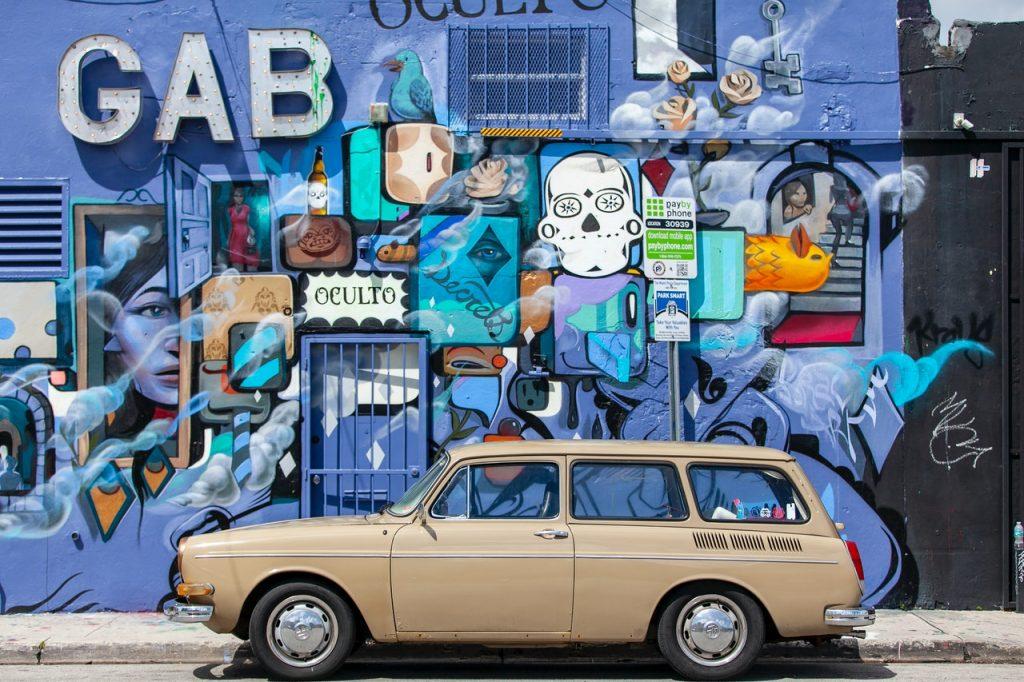 Voiture ancienne devant un mur coloré dans la rue